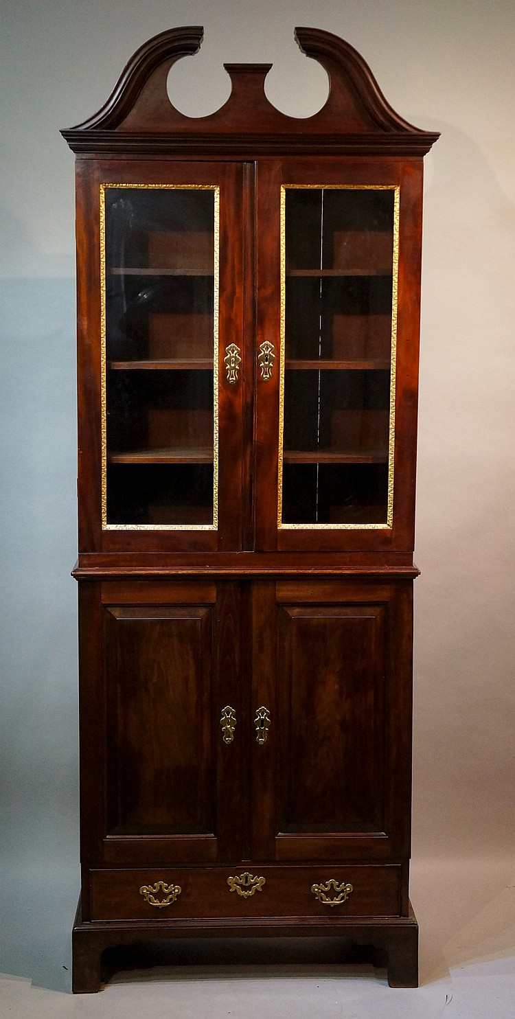 A George II style mahogany bookcase with architectural pediment above a pai