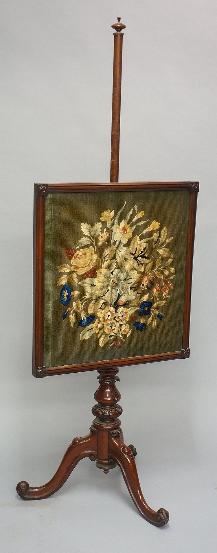 A Victorian mahogany fire screen, the rectangular banner worked in floral g