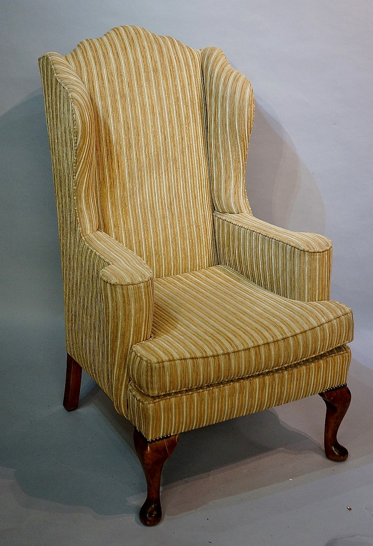 A Victorian wingback armchair in Queen Anne style on cabriole legs with pad