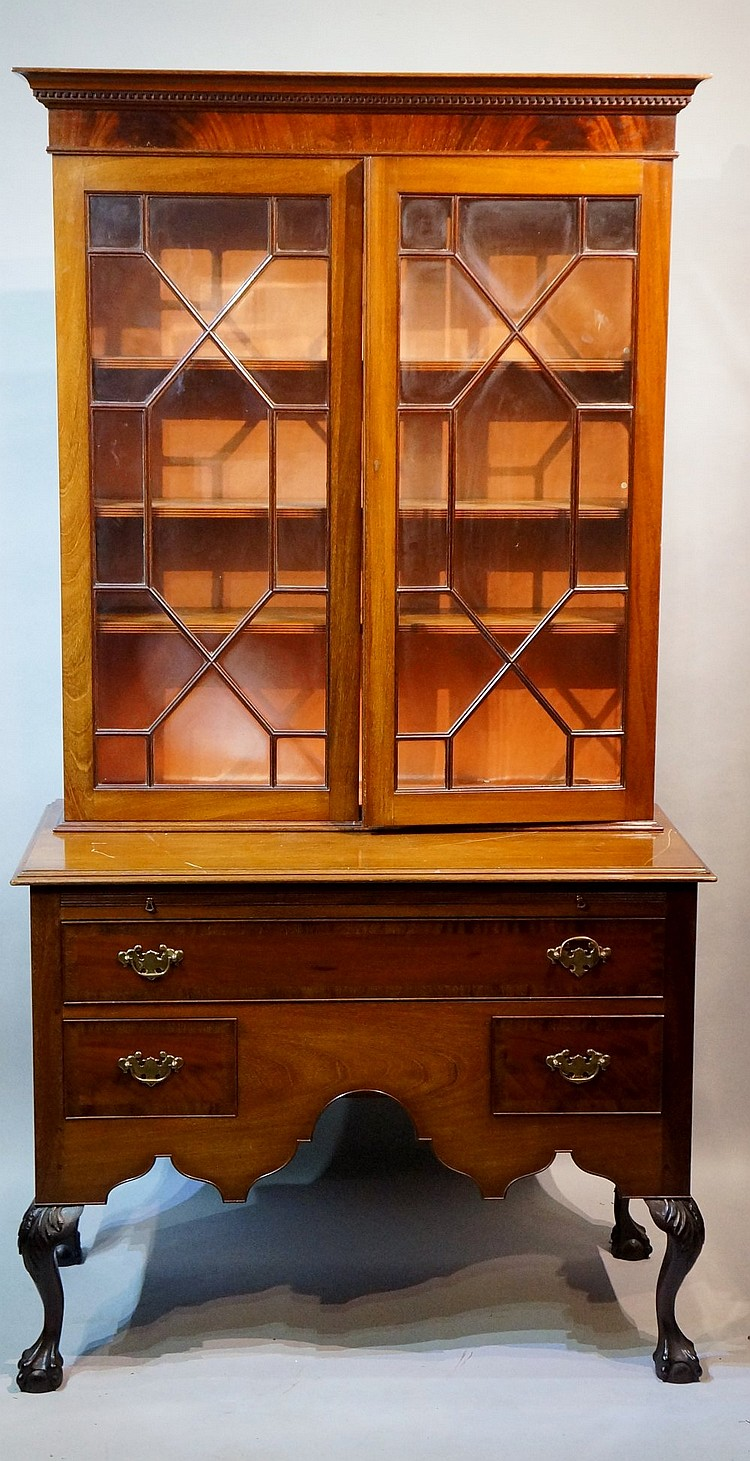 A mahogany bookcase, the top with dentil moulded cornice above a pair of as