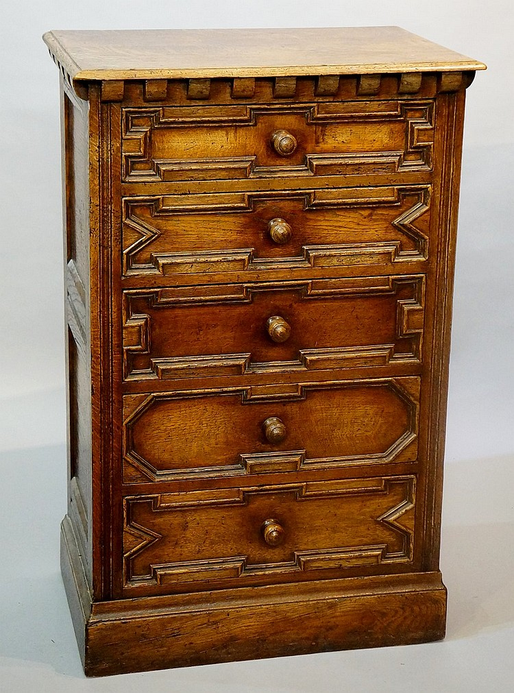 A reproduction small oak chest, five geometric panelled drawers, panelled s