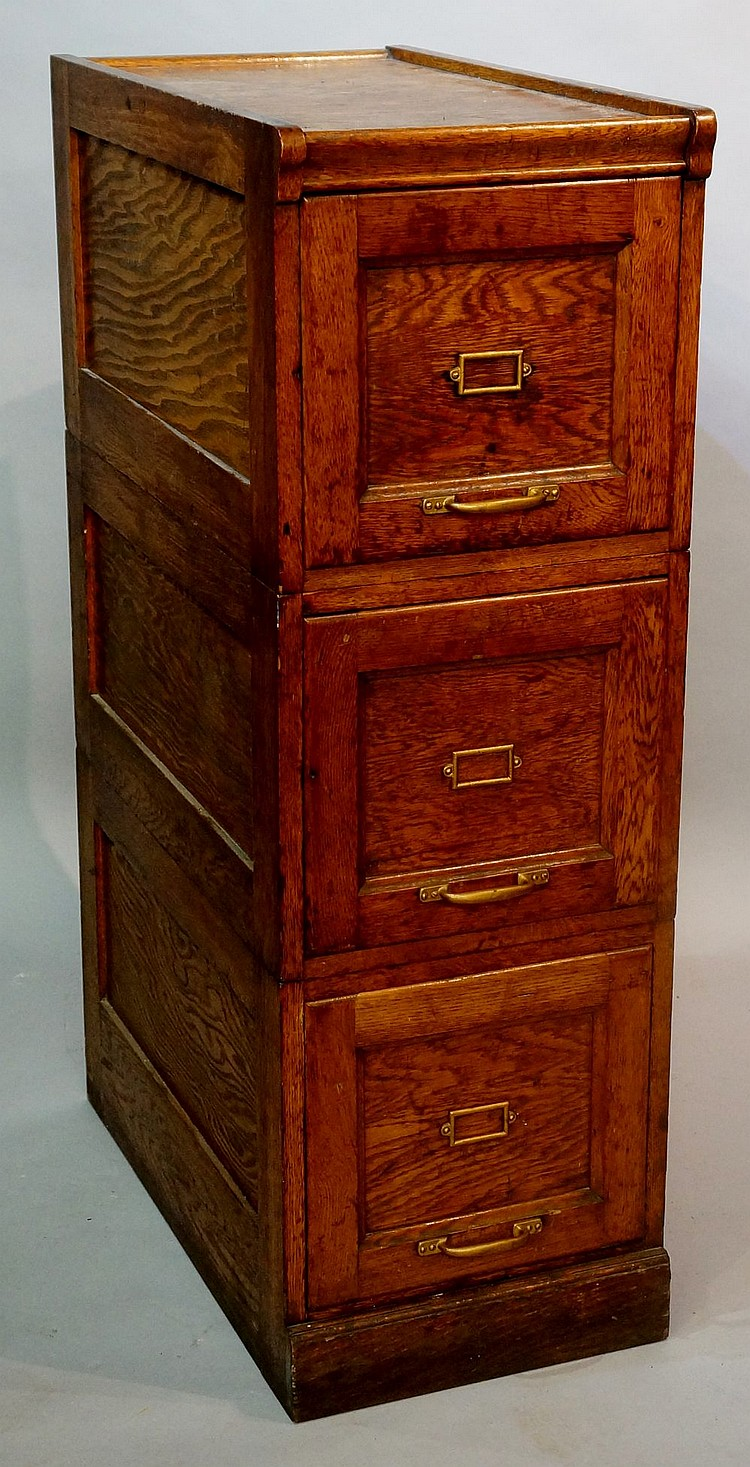 An oak three drawer panelled filing cabinet with gold painted iron mounts,