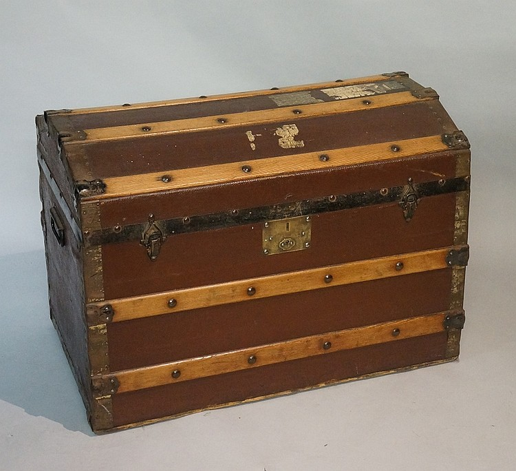 A metal and wooden bound brown fabric covered steamer trunk with domed lid,