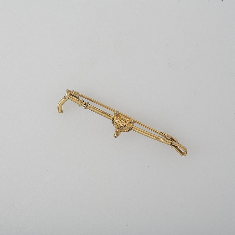 GOLD PIN IN THE FORM OF A RIDING CROP WITH FOX HEAD EMBLEM.