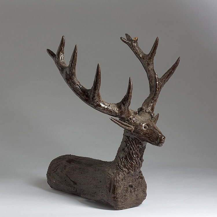 DARK BROWN-GLAZED EARTHENWARE FIGURE OF A RECUMBENT STAG.