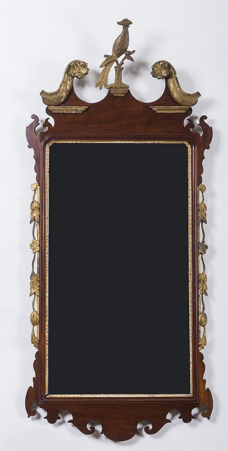 CHIPPENDALE WALNUT AND PARCEL-GILT SCROLL-FORM LOOKING GLASS, THIRD-QUARTER EIGHTEENTH CENTURY.