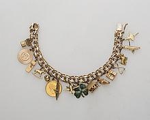 GOLD CHARM BRACELET, AND AN ECLECTIC ASSORTMENT OF CHARMS.