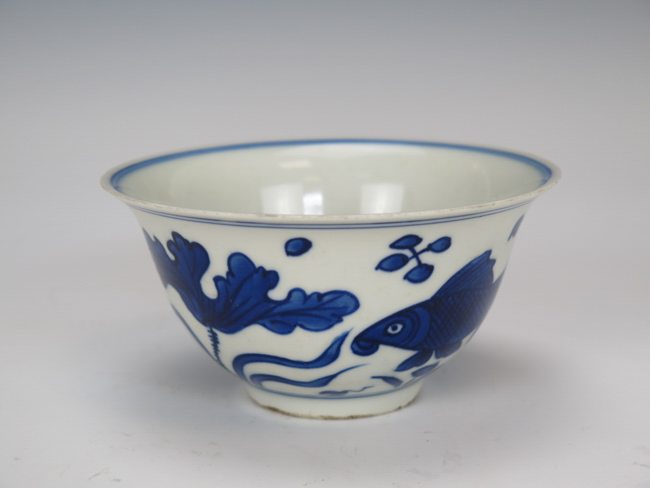 blue and white bowl decorated with fish and lotus