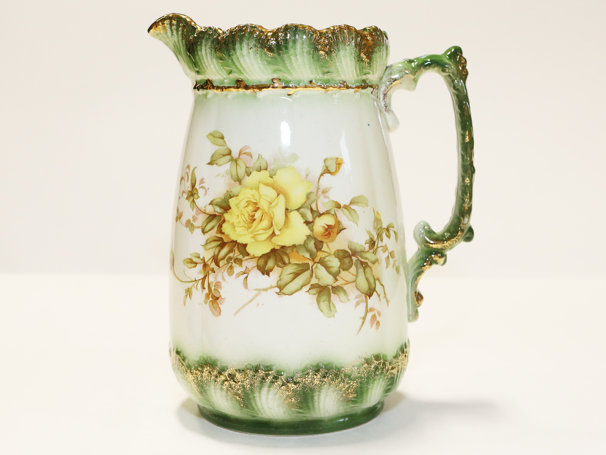 A Green And White Floral Pitcher