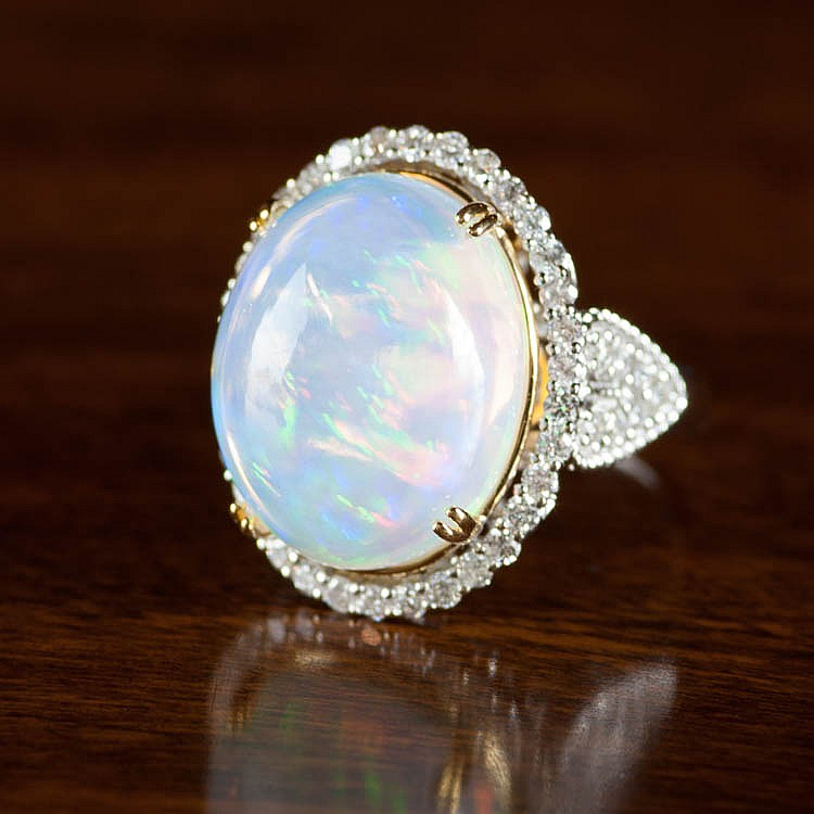 JELLY OPAL AND FOURTEEN KARAT GOLD RING.  The whit