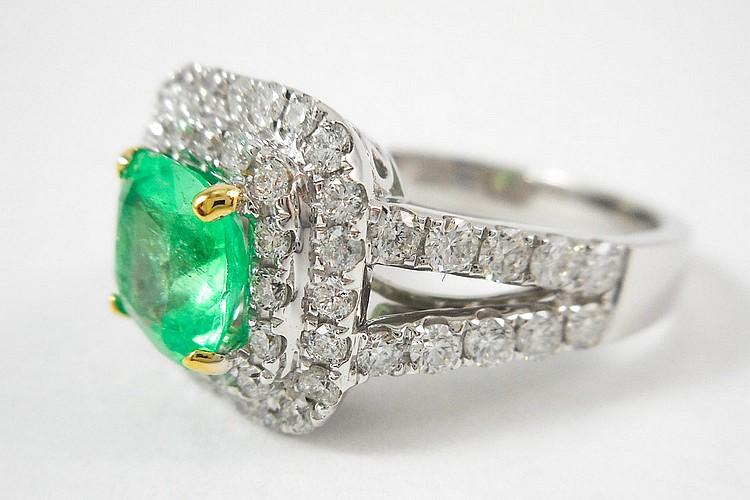 EMERALD, DIAMOND AND EIGHTEEN KARAT GOLD RING. Th