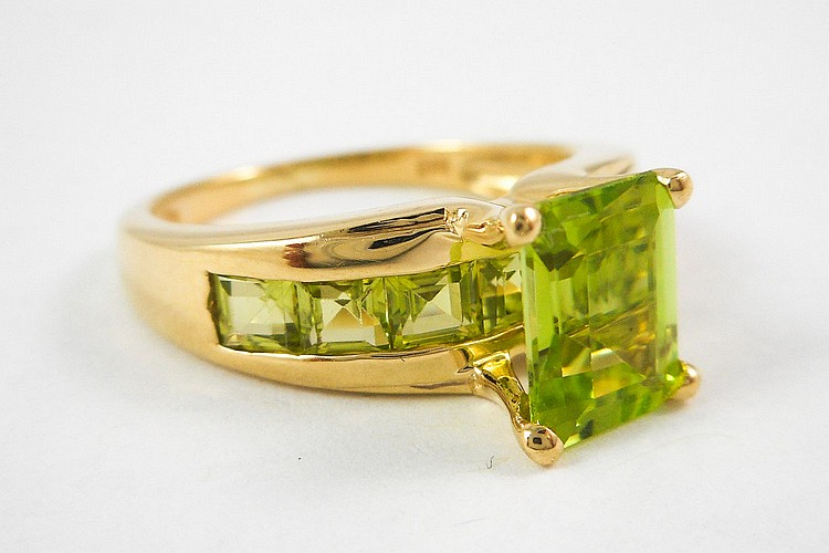 PERIDOT AND TEN KARAT YELLOW GOLD RING, with seven
