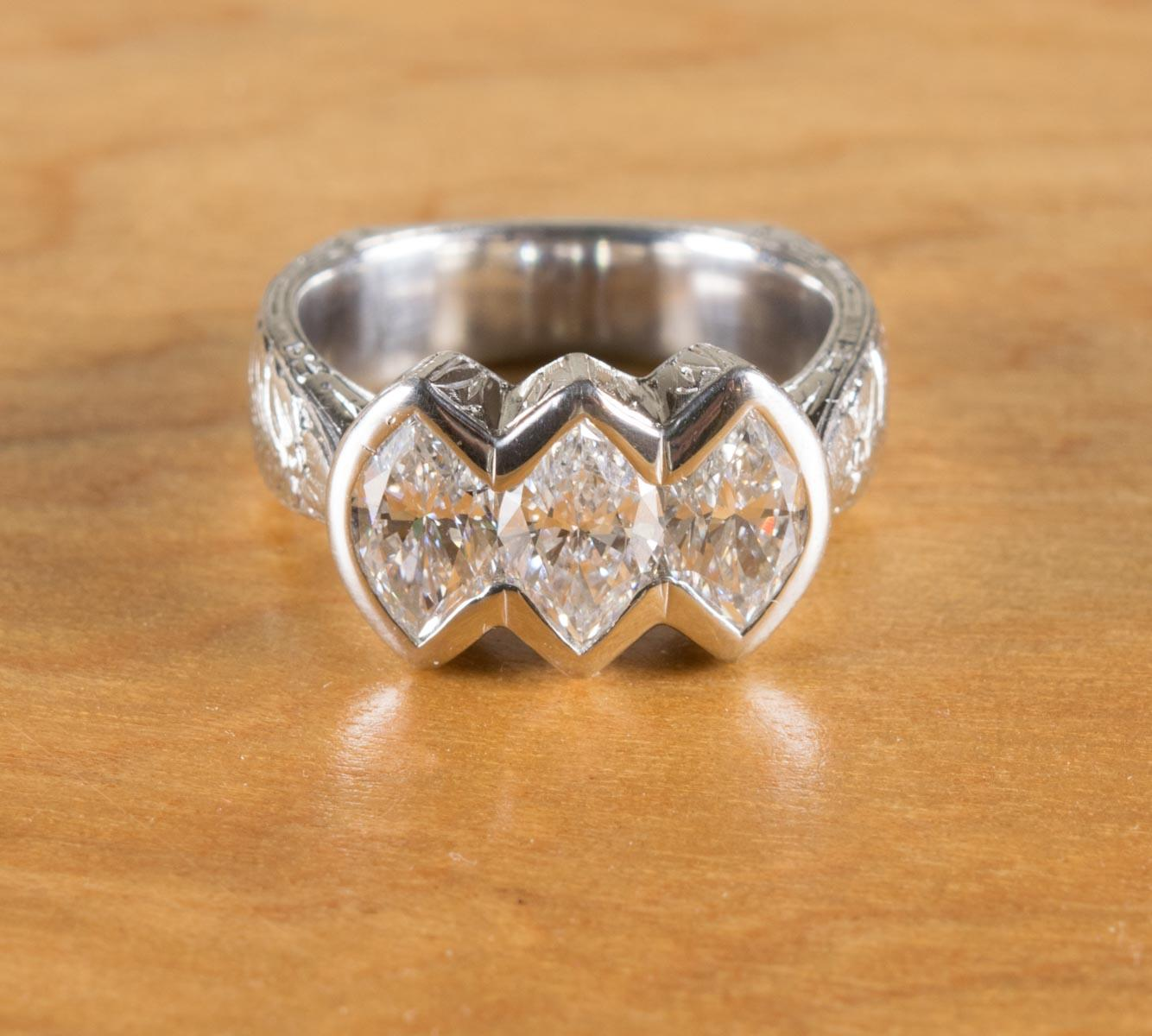 DIAMOND AND PLATINUM THREE-STONE RING. The heavy