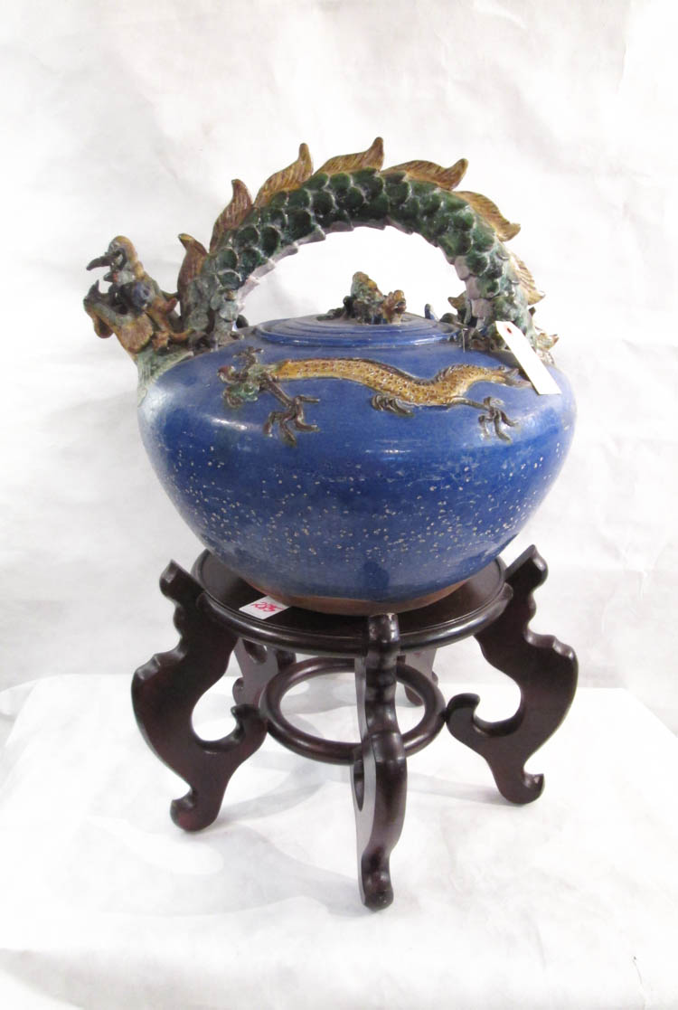 A LARGE CHINESE GLAZED TERRACOTTA TEAPOT ON STAND,
