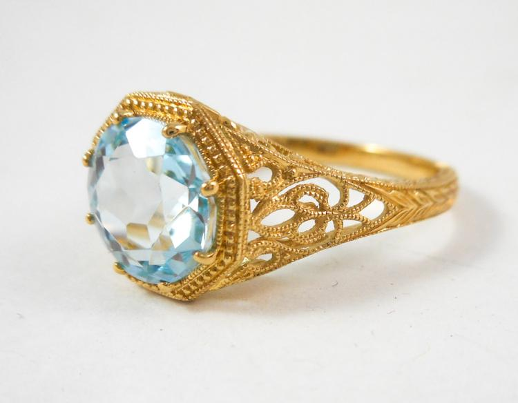 AQUAMARINE AND FOURTEEN KARAT GOLD RING.  The yell