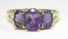 AMETHYST AND TEN KARAT GOLD RING, set with three