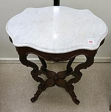 A VICTORIAN MARBLE-TOP WALNUT LAMP TABLE, American, last quarter of the 19th century, having a conformingly shaped white marble top raised on four carved and molded serpentine legs.  Dimensions: 28.5