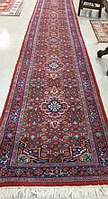 HAND KNOTTED ORIENTAL RUNNER, Indo-Persian, having a row of seven rosette medallions surrounded in Herati floral motif on red ground, 3'0