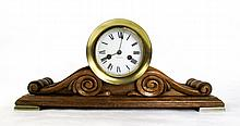 AN AMERICAN BRASS AND CARVED MAHOGANY SHIP'S CLOCK, Waterbury Clock Co., Waterbury, Conn., c. 1900, having a spring wound time/strike movement  in round brass case cradled on a double-scroll mahogany base.  Dimensions: 7.75