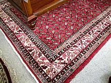 SEMI-ANTIQUE PERSIAN TRIBAL CARPET, Seraband district, central Iran, the rectangular red field covered with repeating rows of individual  stylized flowers, hand knotted wool, 5'6
