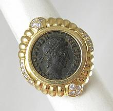 BRONZE COIN, DIAMOND AND EIGHTEEN KARAT GOLD RING, with certificate of authenticity. The 18k yellow gold ring with 16 round-cut diamonds set around a bronze coin of the Roman emperor Constantius II (reigned AD 337-361). Diamond estimated weight: 0.30
