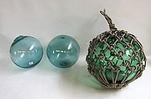 THREE VINTAGE JAPANESE BLOW GLASS FLOATS, blue-green glass, one with original net. Diameters from to inches.
