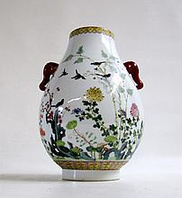 CHINESE HU-SHAPED PORCELAIN VASE, the exterior decorated with colorful enamel birds and flowers on white ground with iron-red elephant head handles, the rim foot centering a blue underglaze Qianlong (1736-1795) reign mark. Height 12 inches.