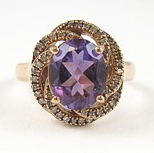 AMETHYST, DIAMOND AND FOURTEEN KARAT ROSE GOLD RING, with round-cut diamonds set around an oval-cut purple amethyst weighing approximately  2.66 cts. Ring size: 7. Complements lots 607 and 608.