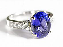 TANZANITE, DIAMOND AND FOURTEEN KARAT GOLD RING. The white and yellow gold ring with six round-cut diamonds set on each side of an oval-cut tanzanite weighing approximately 3.52 cts. Total estimated weight for all twelve diamonds: 0.57 cttw. Ring