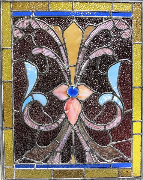"""VICTORIAN STAINED AND LEADED GLASS WINDOW, American, c. 1900, handcrafted with stylized multi-colored floral motif and having a blue """"jeweled"""" accent. The panel measures 23""""L x 18""""W and is set in a custom wood frame."""