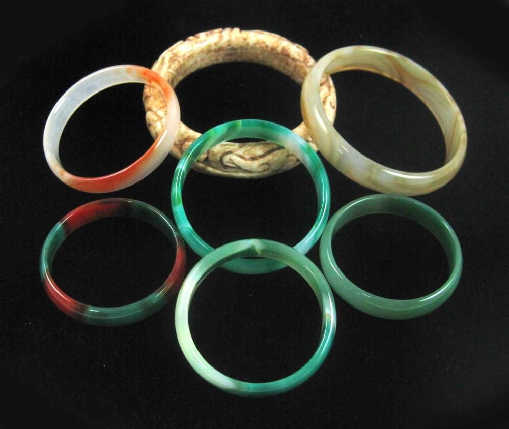 COLLECTION OF SEVEN ROUND BANGLES:  1.) carved opa