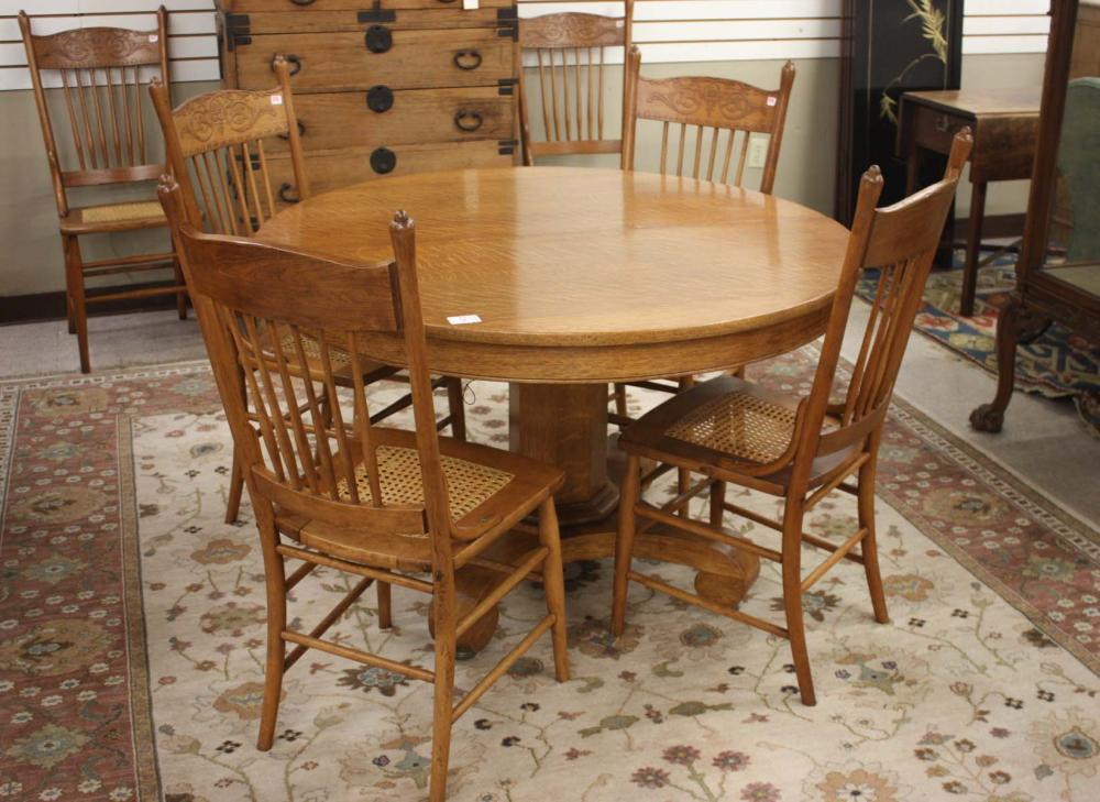 Lot 216: ROUND OAK DINING TABLE AND SIX CHAIRS, Empire Revi