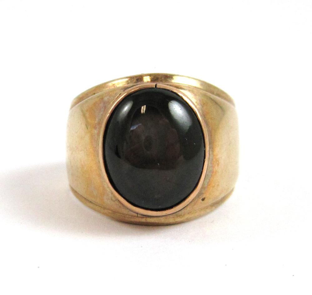 Lot 236: BLACK STAR SAPPHIRE AND YELLOW GOLD RING, with a 1
