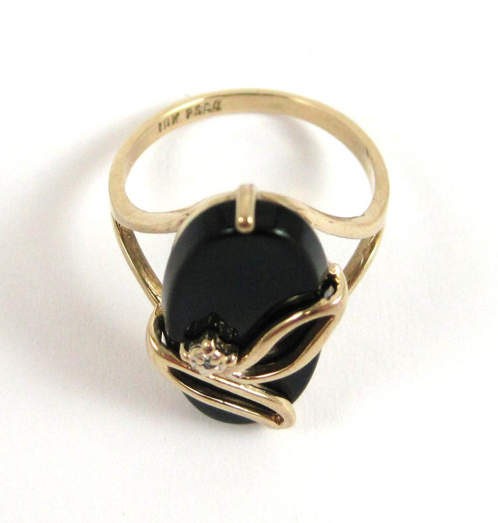 Lot 272: BLACK ONYX, DIAMOND AND YELLOW GOLD RING. The 10k