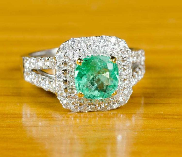 EMERALD, DIAMOND AND EIGHTEEN KARAT GOLD RING. Th