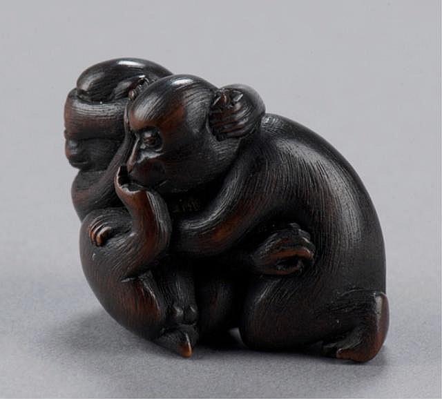 A wood netsuke of two monkeys.