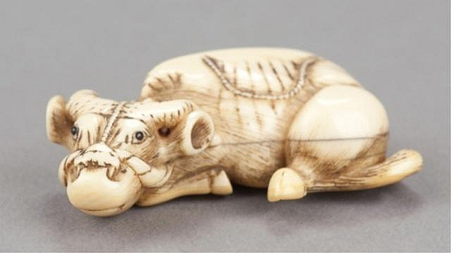 An ivory netsuke of a recumbent ox.