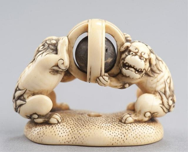 An ivory netsuke of a pair of Shishi.