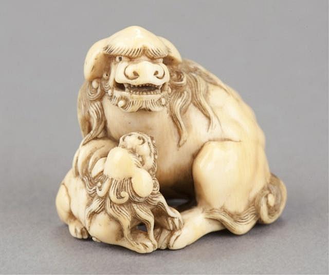 An ivory netsuke of a Shishi with young.