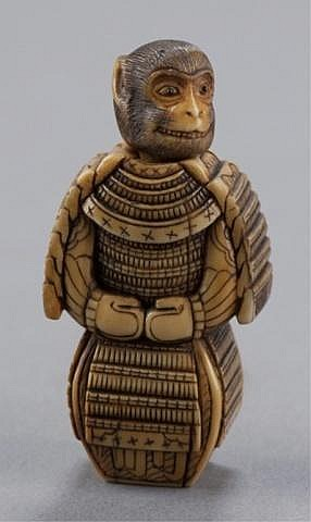 An ivory netsuke of a monkey in a suit of armor.