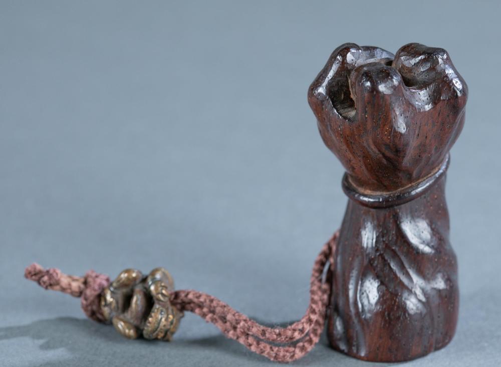 Wood netsuke of severed arm.