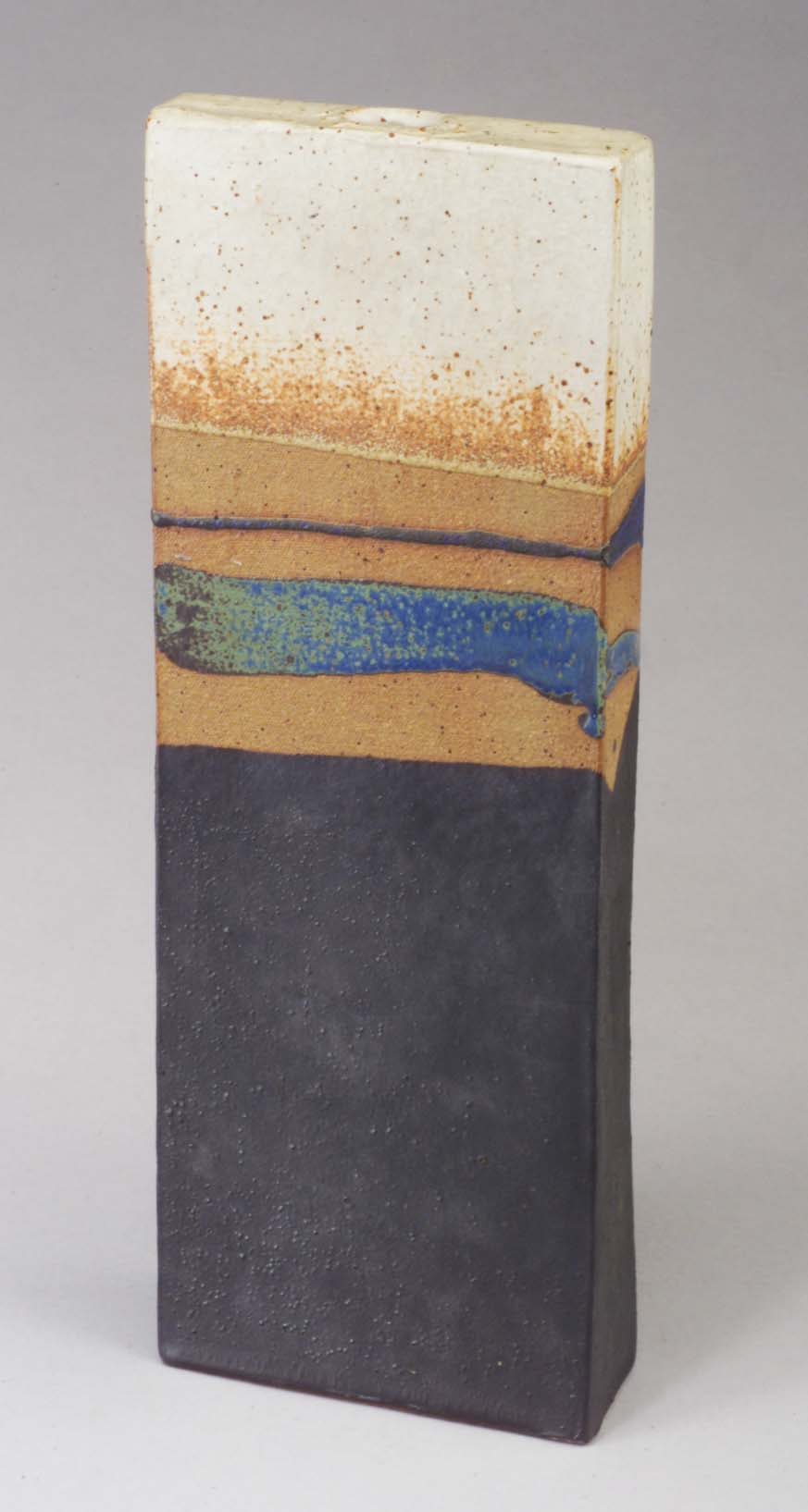 Fine WILLIAM WYMAN (1922-1980) hand-built four-sided stoneware vase, 1967, with random bands in blue and brown over a gunmetal glaze. Incised signature/date. 15