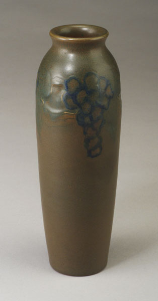 ROOKWOOD Carved Matte ovoid vase by Charles Todd, 1914, with blue grape clusters and leaves on a mottled green and red matte ground. Flame mark/XIV/1844/C.S.T. 10