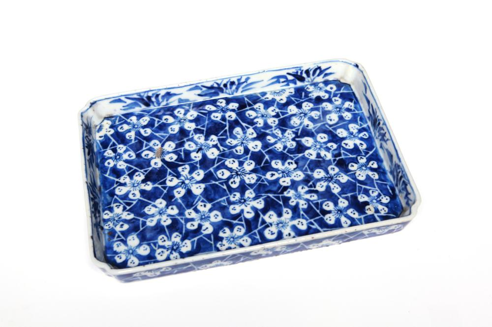 A Blue and white porcelain rectangular teapot tray painted with plum blossoms on a blue ground