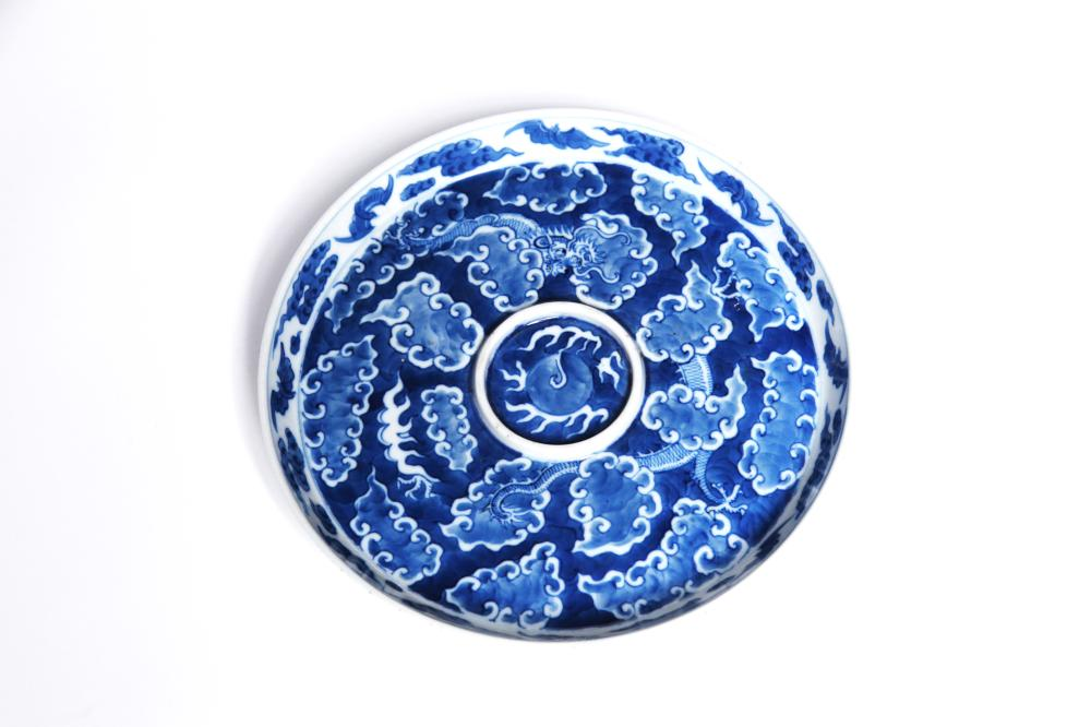 A blue and white porcelain circluar teapot tray painted with a dragon writhing amidst clouds on blue ground
