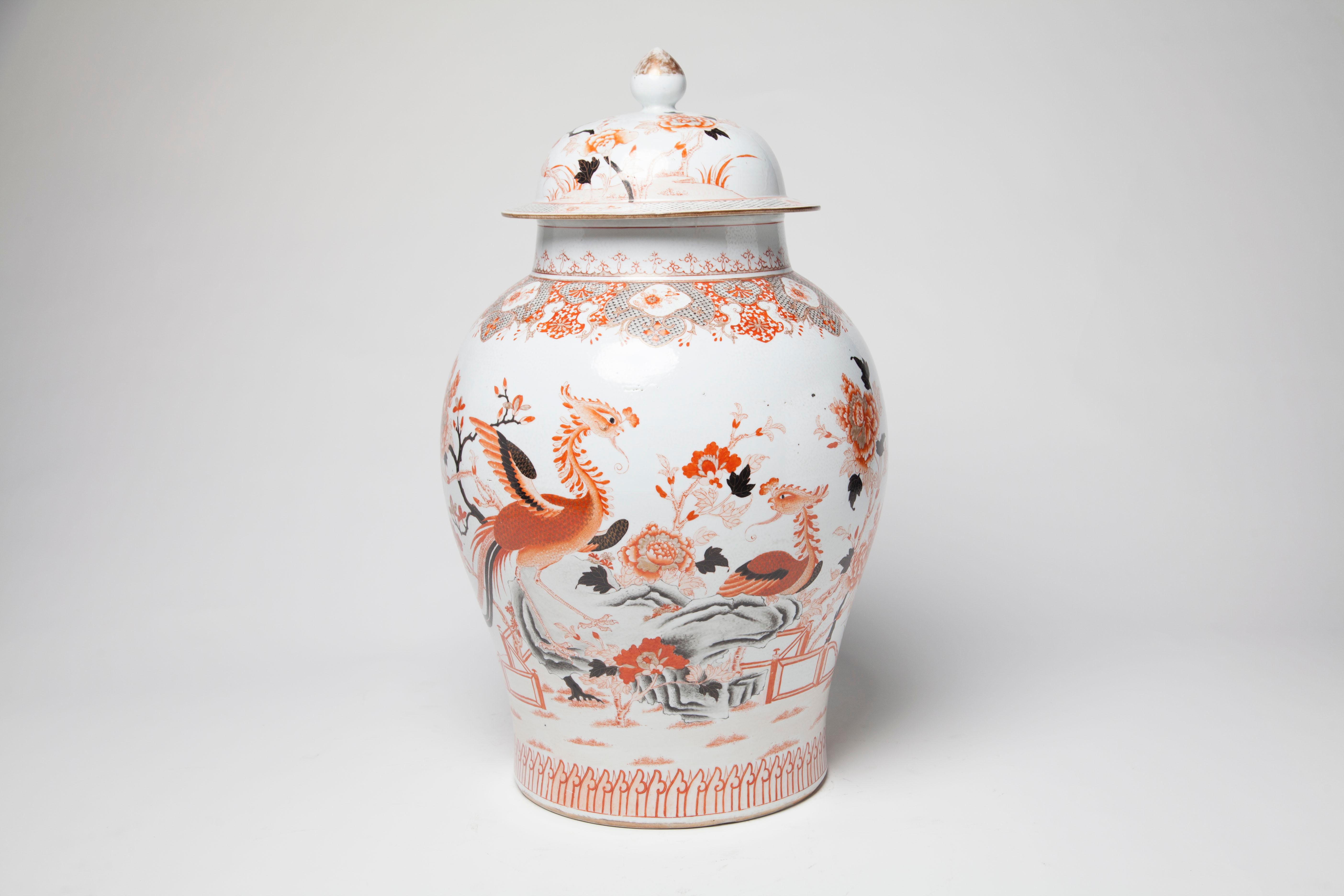 A large polychrome porcelain covered baluster jar painted and gilt with two Phoenixes perched on rockery among blooming peonies on white ground