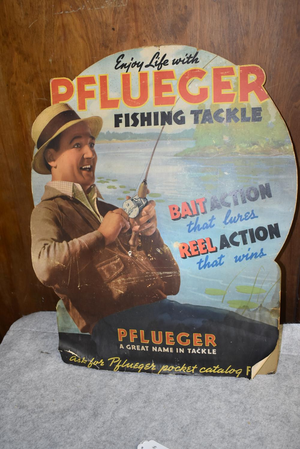 Pflueger die cut cardboard fishing tackle display. Original display w some damage on the bottom. Some small paper chips and Scratches in the center. Display has the easel back display stand