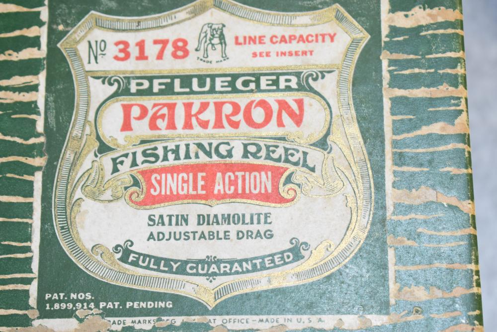 Pflueger Pakron reel in the original box. Reel has double wood handles, No. 3178. Reel appears to be unused. Box shows sign of some soil damage and insect damage. Inspector stamp on bottom reads: 5m12 41