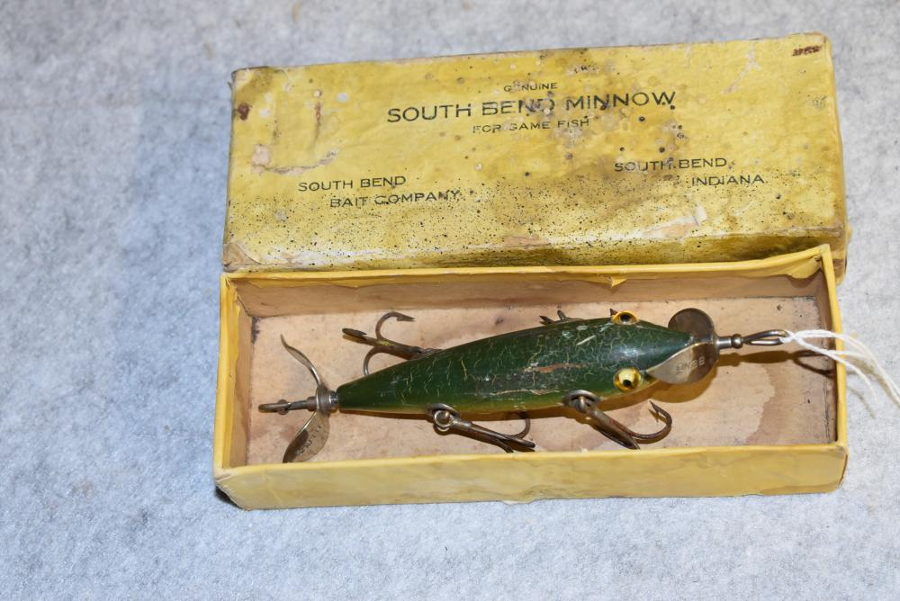 South Bend 5 hook underwater minnow in a box.  Glass eyes w/1 cracked.  NOP.  Tail hook is missing.  Green Crackleback finish.  HPGM.  Hook drags.  Right side paint chip.  Belly chipping.  The South Bend box is just an example.  Unmarked. (F)
