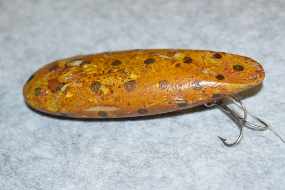 """Miller's Prototype Lure Referred to as the Submarine – Neverfail Finish – Has 1 Belly Hook w/ Screw Eye & Washer Hardware – No Line Tie – Measures 4 1/16"""" in Length – Has the Yellow w/Gold Spots Finish – Blemishes to the Varnish Finish – Unusual Body Shape"""